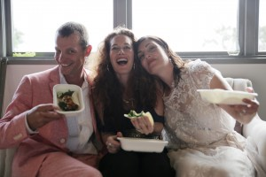 Bride with 2 friends, laughing and sharing food truck catered wedding food together. Bride in white, her female friend in black dress and male friend in salmon linen suit.