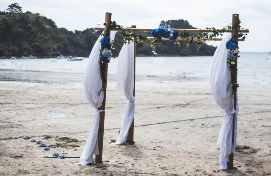 wedding catering waiheke island showing beach scene with Wedding Arbour